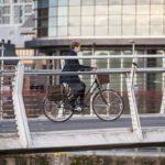 A female cyclist crossing on a bike and pedestrian bridge