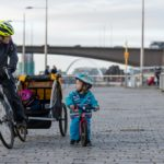 A male cyclist towing a trailer with a child in it, and a small child using a balance bike beside him