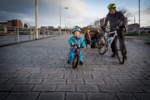 A male cyclist with a small child on a balance bike on a river path. Photo by Andy Catlin