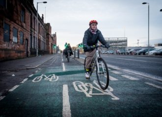 An older female cyclist using a segregated cycle track.