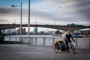 A male cyclist towing a trailer with a small child in it on a river path.