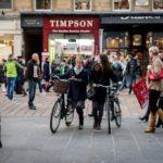 Two women wheeling their bikes through a pedestrianised shopping street.