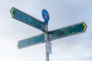 A finger post showing different directions by walking and cycling