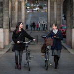 Two women wheeling their bikes through a road closed to through traffic