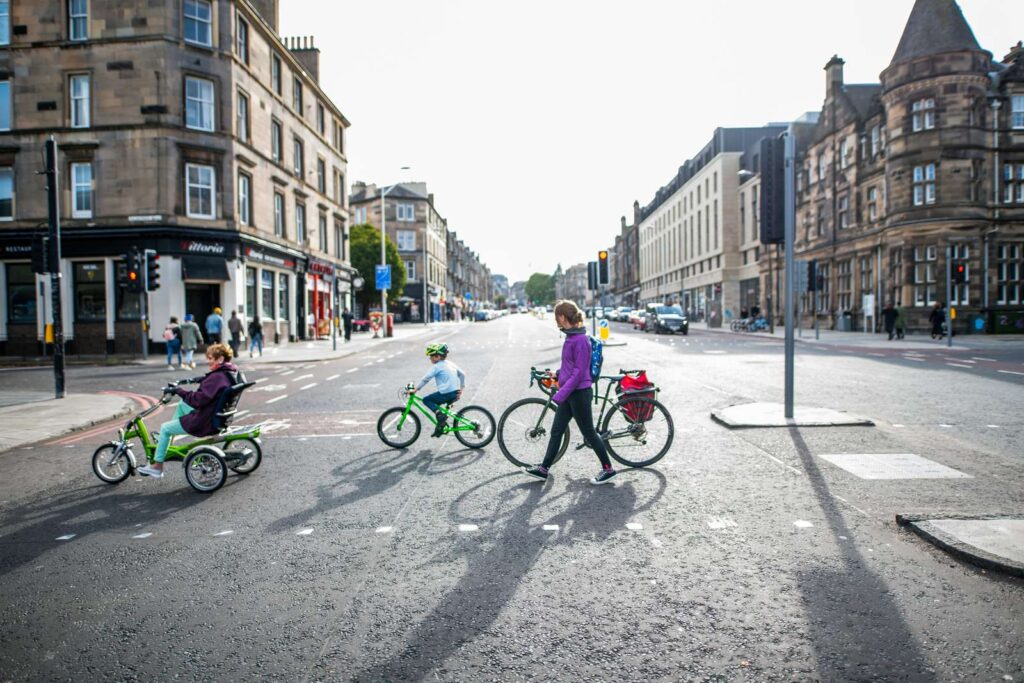 Trike, child and pedestrian using a crossing. Photo by Andy Catlin