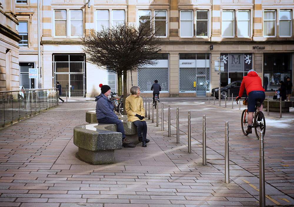 Two people sitting on a bench looking at a cyclist going past. Photo (c) Iona Shepherd