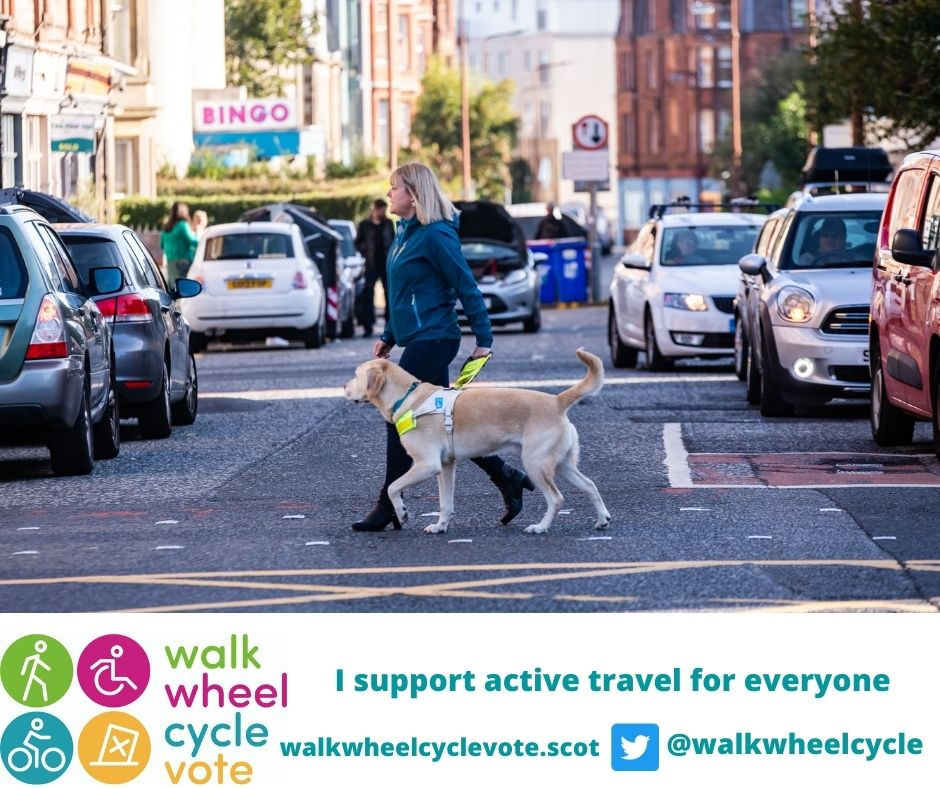 Image of woman crossing road with a guide dog and 'I support active travel for everyone'