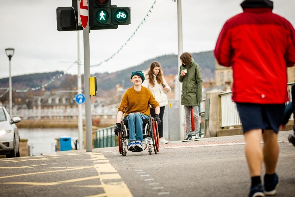 man crossing street in a wheelchair using a crossing