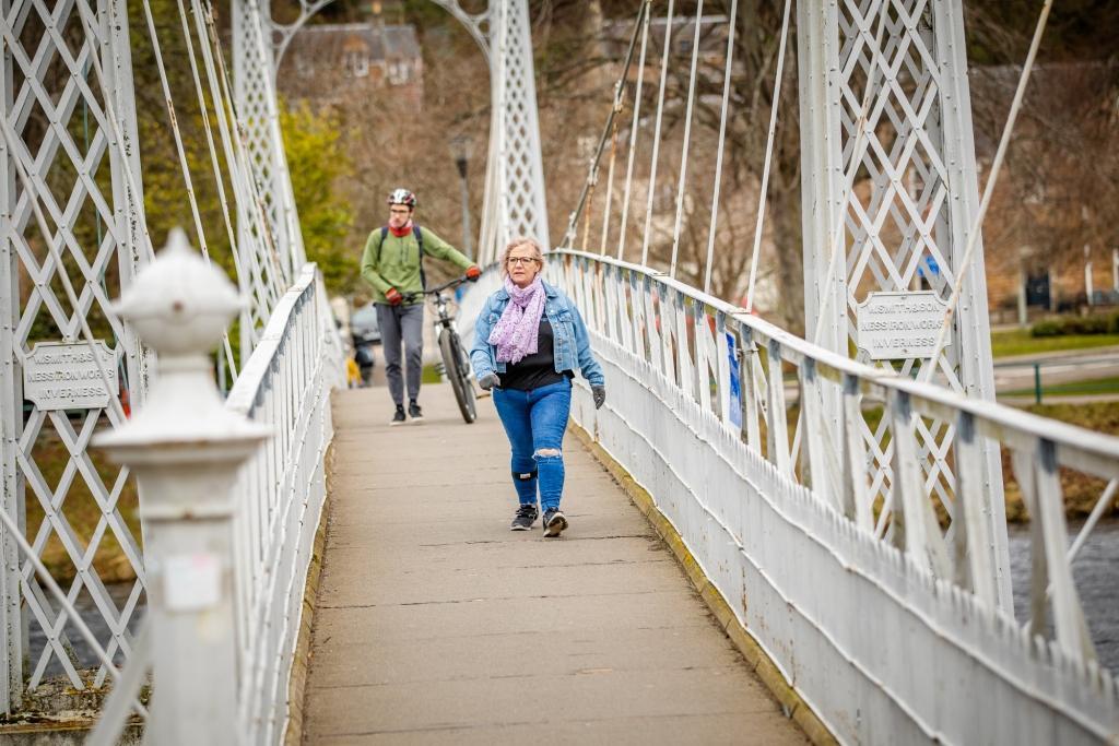 woman walking across pedestrianised bridge